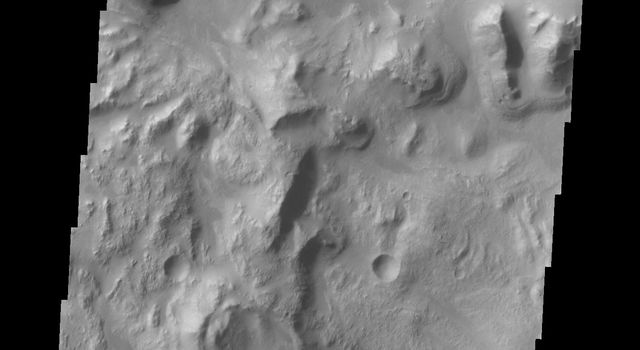 This image captured by shows NASA's 2001 Mars Odyssey the northern wall of Ganges Chasma. Dunes and a landslide deposit of visible at the bottom of the image.
