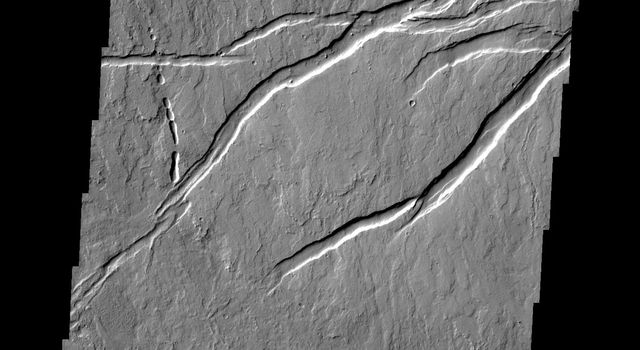 This image taken by NASA's 2001 Mars Odyssey shows lava flows and tectonic features related to the Arsia Mons volcanic system. The tectonic graben (downdropped blocks bounded by faults) are called Oti Fossae.