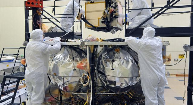 Workers place the special radiation vault for NASA's Juno spacecraft onto the propulsion module. The whole vault, with more than 20 electronic assemblies inside, weighs about 200 kilograms (500 pounds).