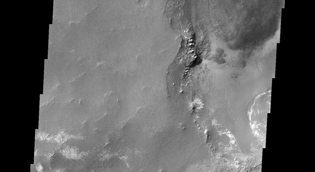 The floor of Melsa Chasma contains a variety of landforms. This image from NASA's 2001 Mars Odyssey shows deposits of fine materials as well as layered deposits.