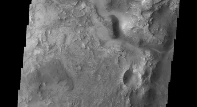 Nili Fossae, a series of tectonic fractures, is the low region on the right side of this image captured by NASA's Mars Odyssey. A small channel is visible draining into the large tectonic depression.