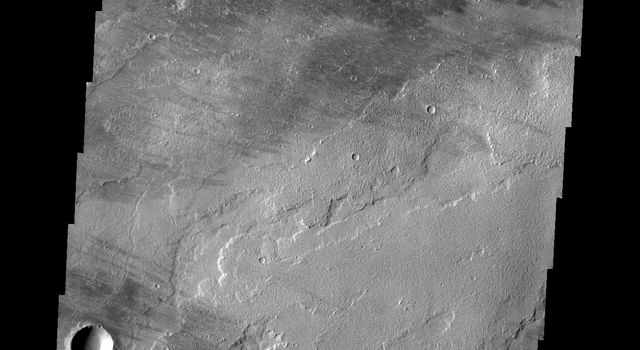 This image from NASA's Mars Odyssey shows are region of lava covered plains east of Olympus Mons. Winds are common in the area and have created windstreaks downwind of craters in the region and on the lava flows.