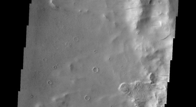 Dark slope streaks mark the rim of this unnamed crater in Terra Sabaea captured by NASA's Mars Odyssey.