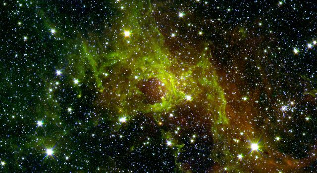 This image from NASA's Spitzer Space Telescope shows a wispy, vast structure in the constellation Perseus with a small bubble right in its center puffed out by spasms of fresh-formed, heavyweight stars.