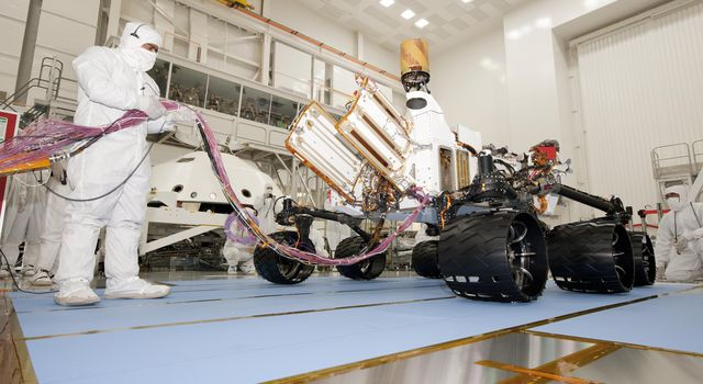 A test operator in clean-room garb holds umbilical cables for NASA's Mars rover Curiosity during the rover's first drive test, on July 23, 2010. NASA will launch Curiosity in late 2011 for arrival at Mars in August 2012.