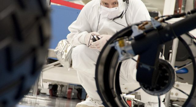 A test operator in clean-room garb observes rolling of the wheels during the first drive test of NASA's Curiosity rover, on July 23, 2010. Technicians and engineers conducted the drive test at the Jet Propulsion Laboratory in Pasadena, Calif.