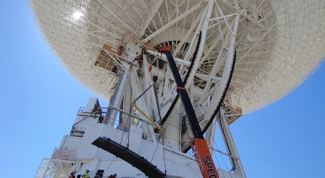 Under the unflinching summer sun, workers at NASA's Deep Space Network complex in Goldstone, Calif., use a crane to lift a runner segment that is part of major surgery on a giant, 70-meter-wide antenna.