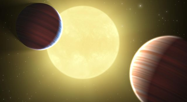 This artist's concept illustrates the two Saturn-sized planets discovered by NASA's Kepler mission. The star system is oriented edge-on, as seen by Kepler, such that both planets cross in front, or transit, their star, named Kepler-9.