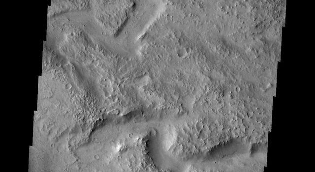 Tikhonravov Crater is a large, old crater in Terra Sabaea. The crater is pockmarked by numerous younger craters and other features. This image from NASA's Mars Odyssey shows a channel within Tikhonravov Crater.
