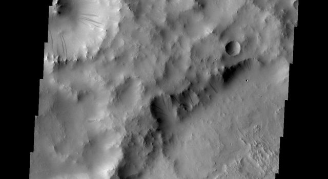 The gravity driven motion of material downhill has swept away some of the bright dust on the rim of this unnamed crater in Terra Sabaea as seen by NASA's Mars Odyssey.