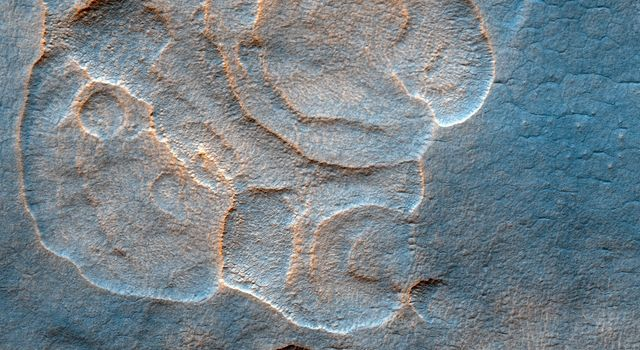The western Utopia Planitia in the Northern mid-latitudes of Mars is marked by a peculiar type of depression with scalloped edges and by a network of polygonal fractures as seen by NASA's Mars Reconnaissance Orbiter.