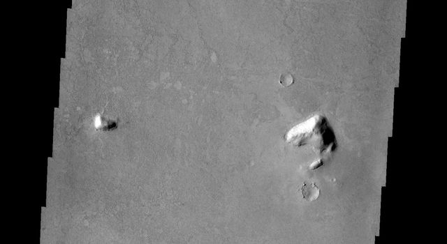 In this image from NASA's Mars Odyssey the majority of the surface appears uniform with a few small hills, the region of fractured blocks sticks out as 'something different,' perhaps remnants of crater ejecta, or an area of a different type of rock.