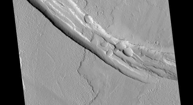 This image from NASA's Mars Reconnaissance Orbiter shows a graben (a trough formed when the ground drops between two parallel faults) and a lava flow in the Tharsis volcanic province of Mars. North is up.