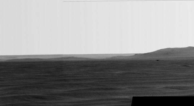 Rising highest above the horizon in the right half of the image, captured by NASA's Mars Exporation Rover, is a portion of the western rim of Endeavour Crater including a ridge informally named 'Cape Tribulation.'