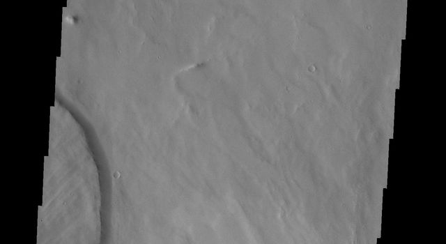 This image from NASA's Mars Odyssey shows a small portion of the northern escarpment of Olympus Mons. The semi-circular deposit on the left side of the frame is a large landslide deposit.