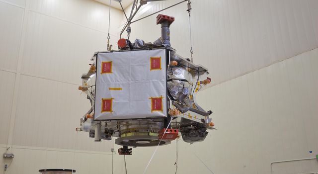 Technicians transfer NASA's Juno spacecraft from its rotation fixture to the base of its shipping container in preparation for a move to environmental testing facilities.