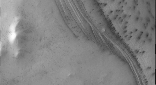 The south polar cap of Mars is comprised of alternating layers of ice and dust. The darker dust layers help show the layering, especially on steep slopes.