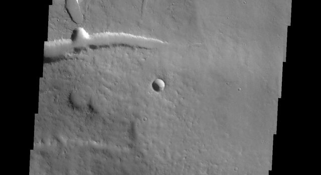 This image from NASA's Mars Odyssey shows part of the eastern flank of Ascraeus Mons, one of the large Tharsis Volcanoes. The circular pits all aligned in a row mark the collapse of the roof of a lava tube.