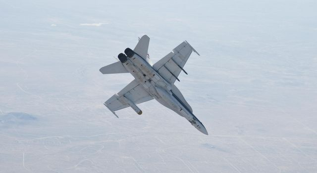 A NASA Dryden Flight Research Center F/A-18 852 aircraft performs a roll during June 2011 flight tests of a Mars landing radar. A test model of the landing radar for NASA's Mars Science Laboratory mission is inside a pod under the aircraft's left wing.