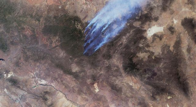 This image from NASA's Terra spacecraft shows the Wallow and Horseshoe 2 Fires burning in Arizona. The data were acquired mid-morning on June 7, 2011. Nearly 10 distinct bluish-colored smoke plumes can be seen blowing toward the upper right (northeast).