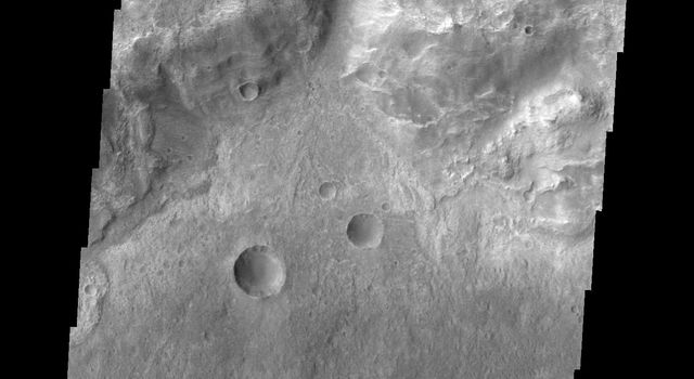 This small channel dissects the rim of an unnamed crater north of Terby Crater and Hellas Planitia as seen by NASA's 2001 Mars Odyssey spacecraft.