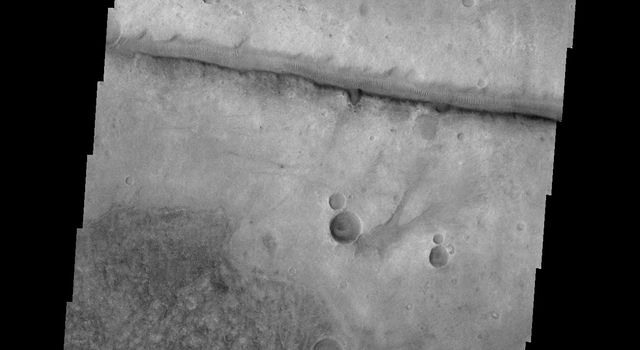 This image from NASA's 2001 Mars Odyssey spacecraft shows a fracture north of Argyre Planitia. Note the dunes within the channel.