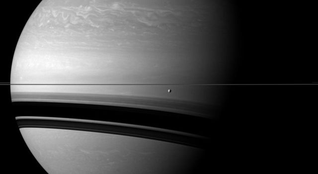 Saturn's moon Tethys orbits in front of the wide shadows cast by the rings onto the planet for this view from NASA's Cassini spacecraft. Tethys appears just below the rings near the center of the image.