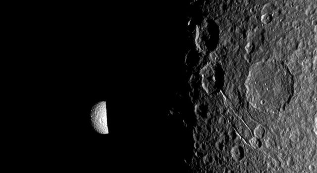Saturn's moon Mimas peeks out from behind the night side of the larger moon Dione in this image captured by NASA's Cassini spacecraft during the Dione flyby of Dec. 12, 2011.