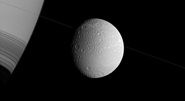Saturn and Dione appear askew in this view from NASA's Cassini spacecraft, with the north poles rotated to the right, as if they were threaded along on the thin diagonal line of the planet's rings.