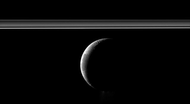 A crescent Enceladus appears with Saturn's rings in this view of the moon from NASA's Cassini spacecraft. The famed jets of water ice emanating from the south polar region of the moon are faintly visible here.