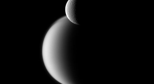 Craters appear well defined on icy Rhea in front of the hazy orb of the much larger moon Titan in this view from NASA's Cassini spacecraft.