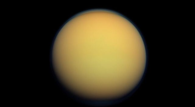 Titan's atmosphere makes Saturn's largest moon look like a fuzzy orange ball in this natural color view from NASA's Cassini spacecraft. Titan's north polar hood is visible at top, and a faint blue haze also can be detected above the south pole at bottom.
