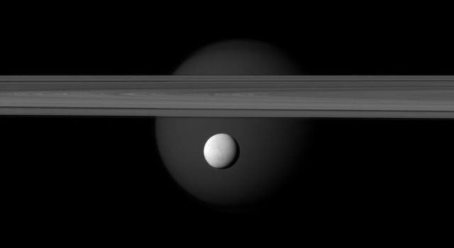 The brightly reflective moon Enceladus appears before Saturn's rings while the larger moon Titan looms in the distance. Jets of water ice and vapor emanating from the south pole of Enceladus (hinting at subsurface sea rich in organics).