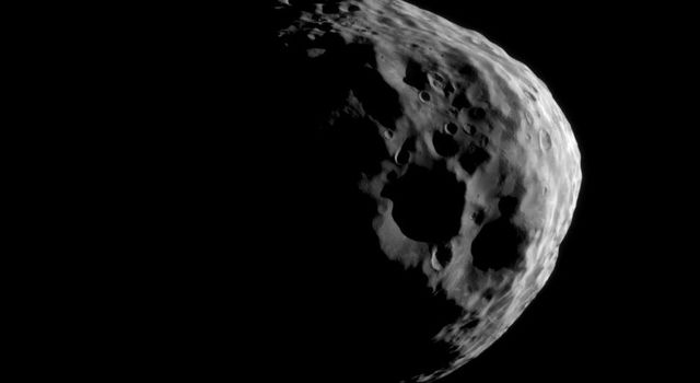 Shadows darken parts of some of Janus' large craters as NASA's Cassini takes a close look during its flyby of this Saturnian moon on March 27, 2012.
