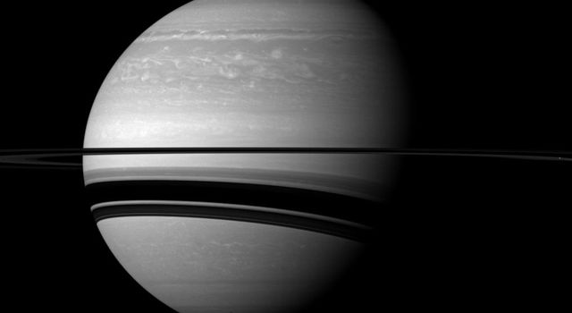Saturn's rings cast wide shadows on the planet, and the shadow of a moon also graces the gas giant in this scene from NASA's Cassini spacecraft. The moon Enceladus is not shown in this view, but it does cast a small, elongated shadow.