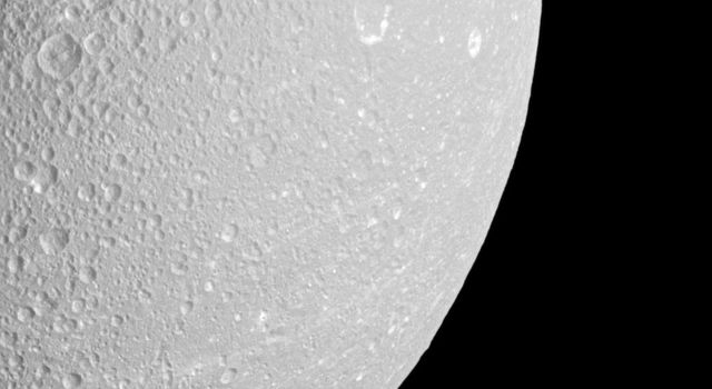 Saturn's moon Mimas peeps out from behind the larger moon Dione in this view from NASA's Cassini spacecraft.