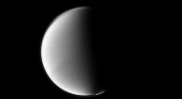 Titan's south polar vortex seems to float above the moon's south pole in this Cassini spacecraft view. The vortex, which is a mass of gas swirling around the south pole high in the moon's atmosphere, can be seen in the lower right of this view.