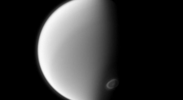 NASA's Cassini spacecraft spies Titan's south polar vortex from below the moon in this image. Imaging scientists are monitoring the vortex to study its seasonal development.