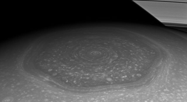 Saturn's north polar hexagon basks in the Sun's light now that spring has come to the northern hemisphere. Many smaller storms dot the north polar region and Saturn's signature rings put in an appearance in the background.