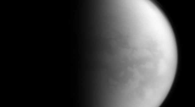 NASA's Cassini spacecraft peers through Titan's thick clouds to spy on the region dubbed 'Senkyo' by scientists. The dark features include vast fields of dunes, composed of solid hydrocarbon particles precipitated out of Titan's atmosphere.