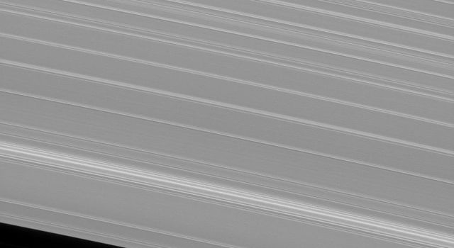 The shepherd moon Pan orbits Saturn in the Encke gap while the A ring surrounding the gap displays wave features created by interactions between the ring particles and Saturnian moons in this image from NASA's Cassini spacecraft.