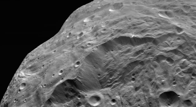 NASA's Dawn spacecraft obtained this image of the giant asteroid Vesta with its framing camera on Aug. 26, 2011. The detail in this image shows a steep scarp with landslides and vertical craters in the scarp wall.