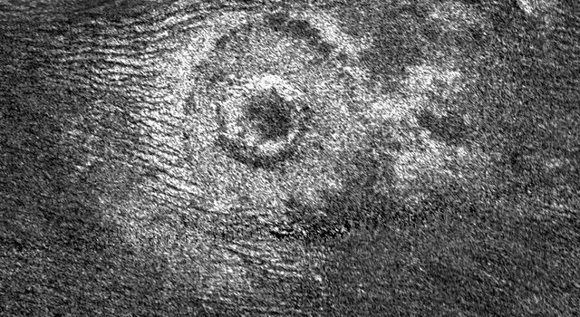 Impact craters are rare on Titan. Until recently only seven had been identified definitely on Titan. Dunes, visible as dark lines on the left of the image, have been swept toward the crater by the winds of Titan.