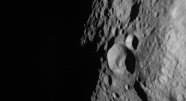 NASA's Dawn spacecraft obtained this image of a young and old crater at the night and day boundary on asteroid Vesta. The image has a resolution of about 260 meters per pixel.