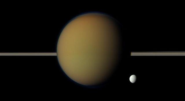 Saturn's moon Tethys, with its stark white icy surface, peeps out from behind the larger, hazy, colorful Titan in this view of the two moons obtained by NASA's Cassini spacecraft. Saturn's rings lie between the two.