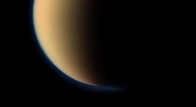 This view from NASA's Cassini spacecraft look toward the south polar region of Saturn's largest moon, Titan, and show a depression within the moon's orange and blue haze layers near the south pole.