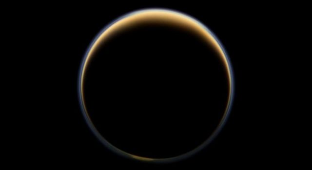 NASA's Cassini spacecraft looks toward the night side of Saturn's largest moon and sees sunlight scattering through the periphery of Titan's atmosphere and forming a ring of color.