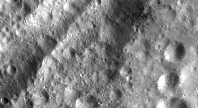 This closeup of asteroid Vesta from NASA's Dawn spacecraft shows small scale features such as grabens (linear depressions) which run parallel to and inside the troughs.