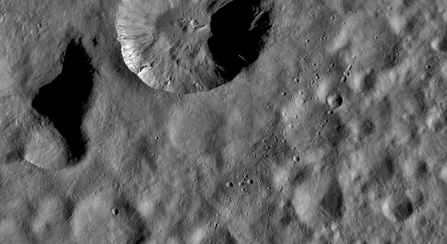 This image from NASA's Dawn spacecraft is dominated by a wide, young, fresh crater on asteroid Vesta. Surrounding this crater is its ejecta blanket, a covering of small particles that were thrown out during the impact that formed the crater.