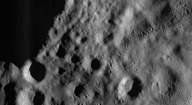 This image from NASA's Dawn spacecraft shows a part of the surface of asteroid Vesta, which is mantled (covered) by an ejecta blanket, evident as smoothly textured surface visible across the image.